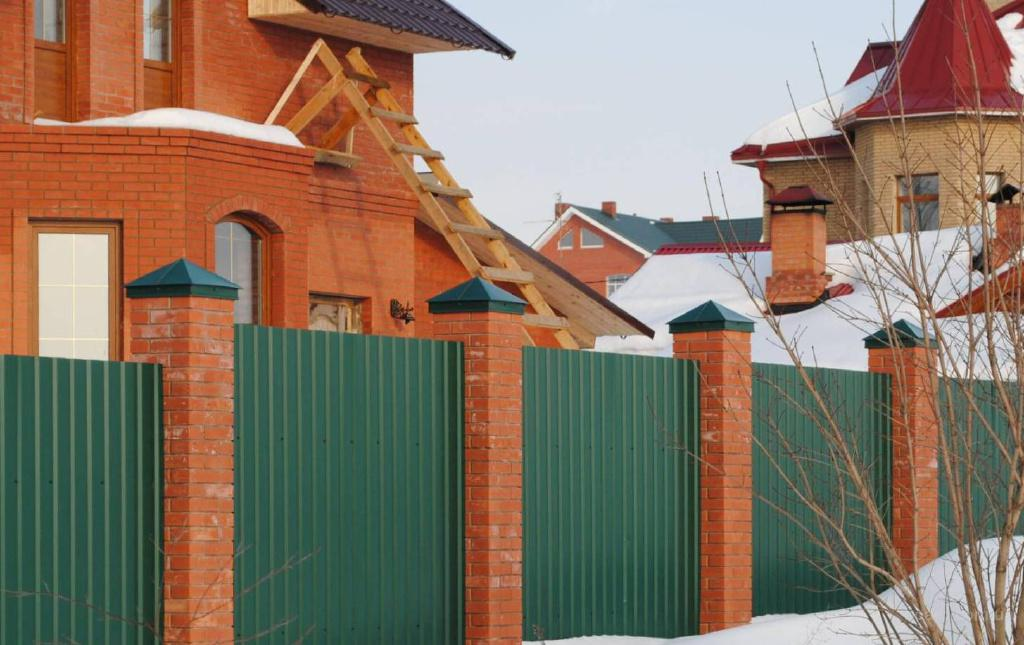 Забор из металлопрофиля зеленого цвета.